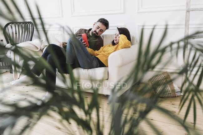Pareja sentada en el sofá en el salón de la casa nueva mirando al teléfono celular - foto de stock