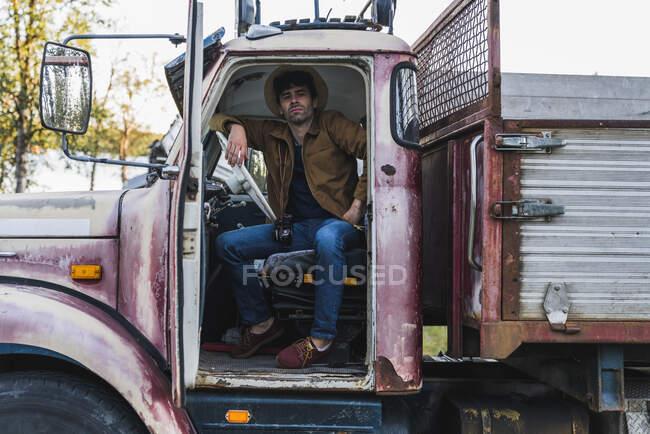 Крутий молодий чоловік, що сидить у розбитій вантажівці. — стокове фото