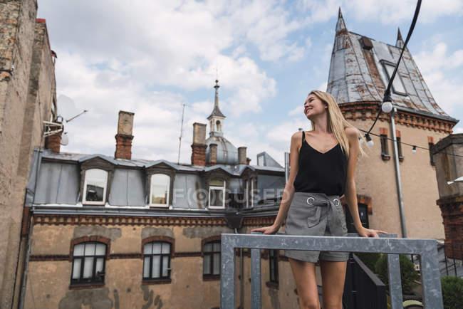 Junge Frau steht auf Balkon und genießt frische Luft — Stockfoto