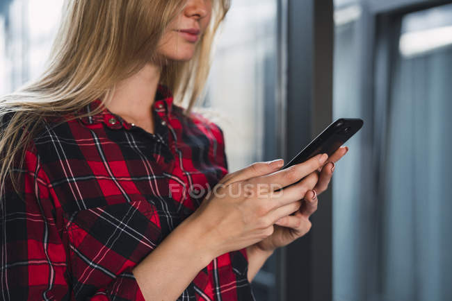 Hands of young woman holding smartphone, partial view — Stock Photo