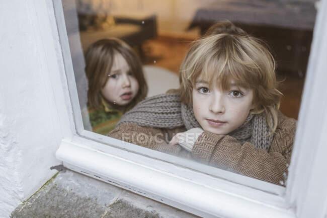 Retrato del niño mirando fuera de la ventana con su hermana pequeña en el fondo. - foto de stock
