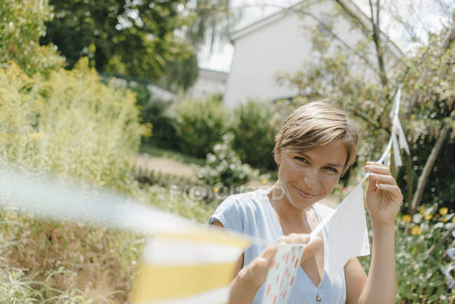 Portrait of smiling woman hanging up pennants in garden — Stock Photo
