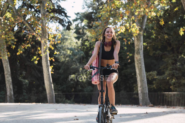 Fit молодая женщина, перевозящих йога коврик, езда на велосипеде — стоковое фото