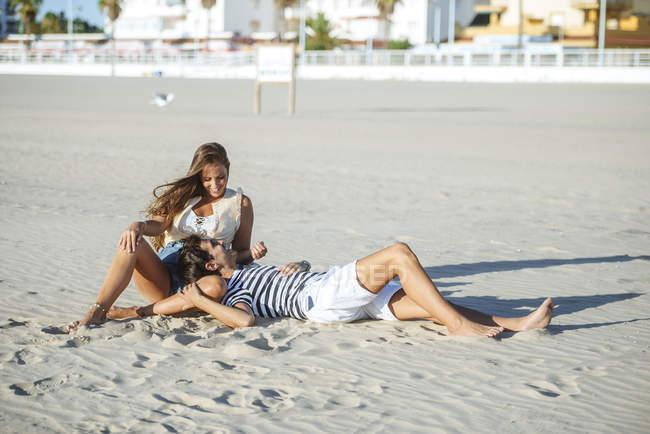 Heureux jeune couple affectueux sur la plage — Photo de stock