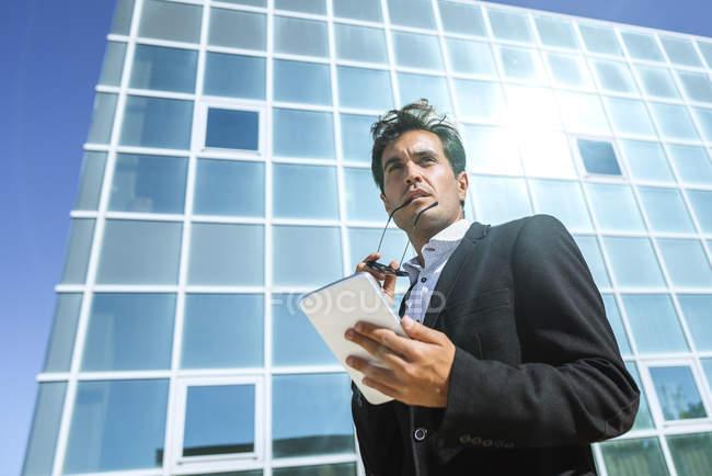 Homme d'affaires avec tablette et lunettes de soleil à l'extérieur du bâtiment de bureaux — Photo de stock