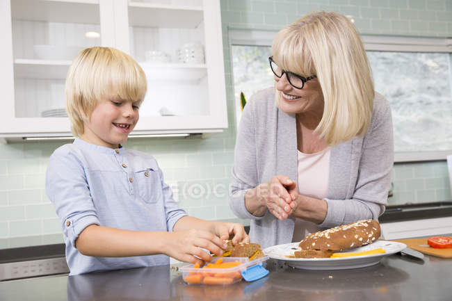 Grandmother and grandson preparing lunch box in kitchen together — Stock Photo