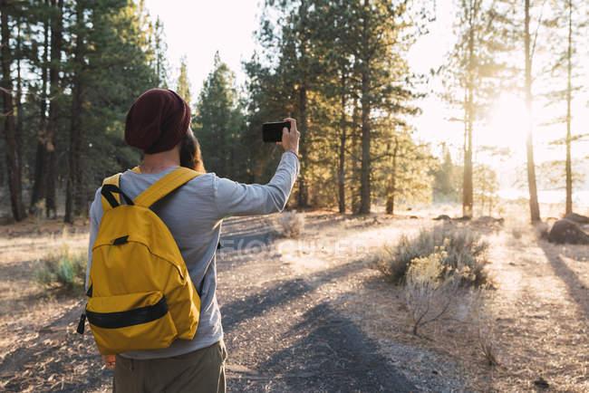 Estados Unidos, norte de California, joven tomando una selfie en un bosque cerca del Parque Nacional Volcánico Lassen - foto de stock