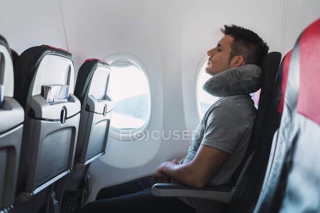 Homme dormant avec un oreiller de cou dans un avion — Photo de stock
