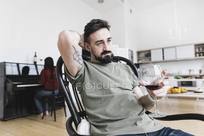 Пара дома, мужчина пьет вино, женщина играет на фортепиано на заднем плане — стоковое фото