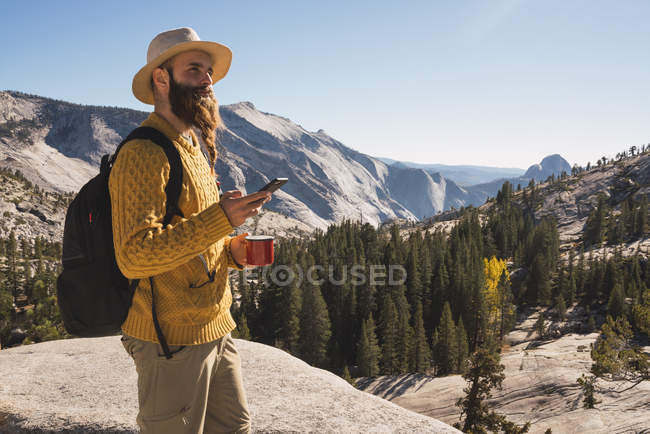 USA, California, Yosemite National Park, hiker using smartphone and holding cup — Stock Photo
