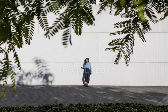 Geschäftsfrau mit Smartphone, Laptoptasche in der Hand — Stockfoto
