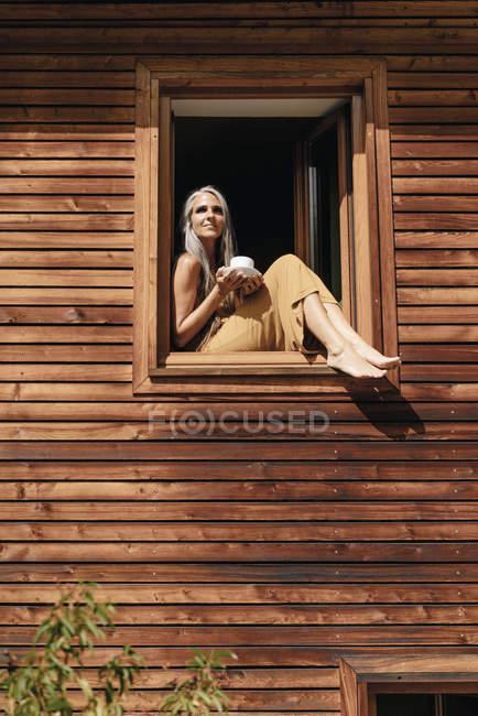 Femme avec une tasse de café assis sur le rebord de la fenêtre de sa maison et bronzer — Photo de stock