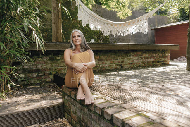 Portrait of smiling woman sitting barefoot on terrace in the backyard — Stock Photo