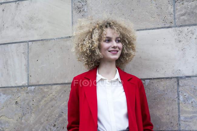 Портрет усміхнена білява жінка з локони носити червоний костюм пальто — стокове фото