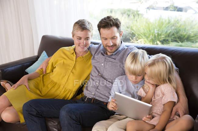 Familie sitzt zu Hause auf Couch und nutzt Tablet — Stockfoto