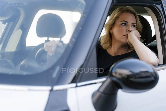 Bored woman looking out of car window — Stock Photo