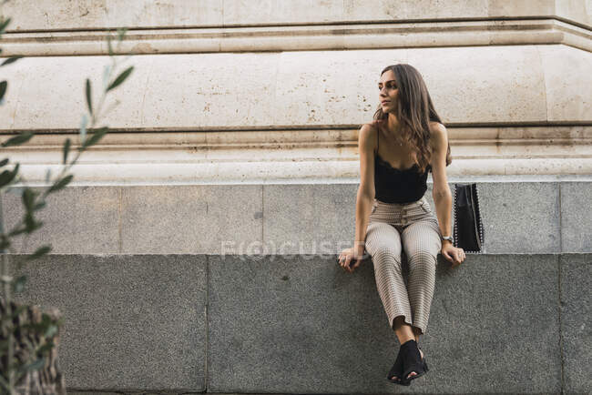 Young woman sitting on a wall waiting — Stock Photo