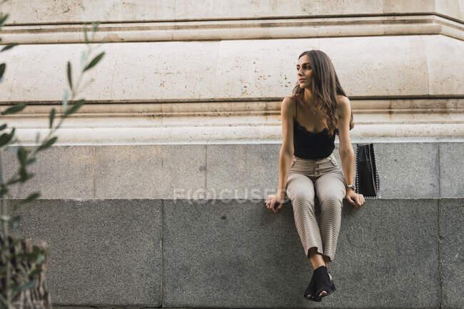 Молода жінка сидить на стіні і чекає. — стокове фото