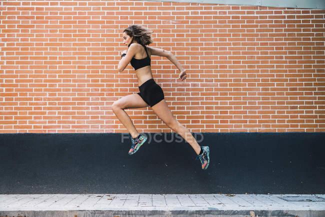 Подходящая молодая женщина бегает и прыгает в парке — стоковое фото