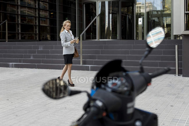 Senior businesswoman checking cell phone outside office building — Stock Photo