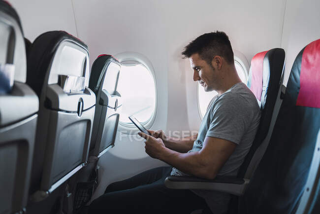 Man using ebook in airplane — Stock Photo