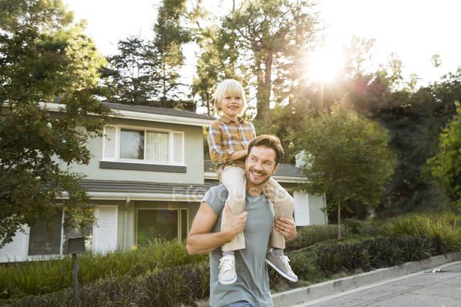 Menino feliz nos ombros do pai na frente de sua casa — Fotografia de Stock