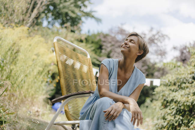 Relaxed woman sitting in garden on chair with closed eyes — Stock Photo