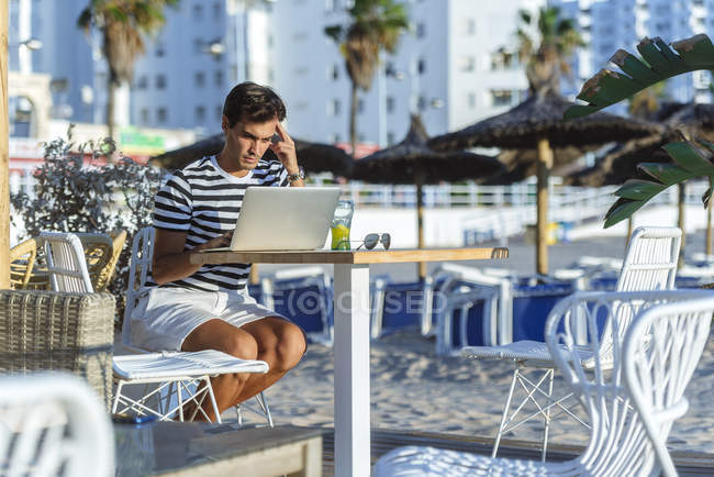 Man with laptop sitting on the terrace of a beach bar — Stock Photo