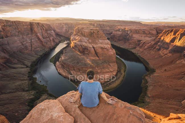 Usa, Arizona, Colorado River, Horseshoe Bend, joven sentado en el mirador. - foto de stock