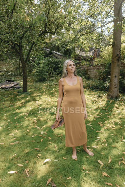 Woman standing barefoot in the garden and relaxing — Stock Photo