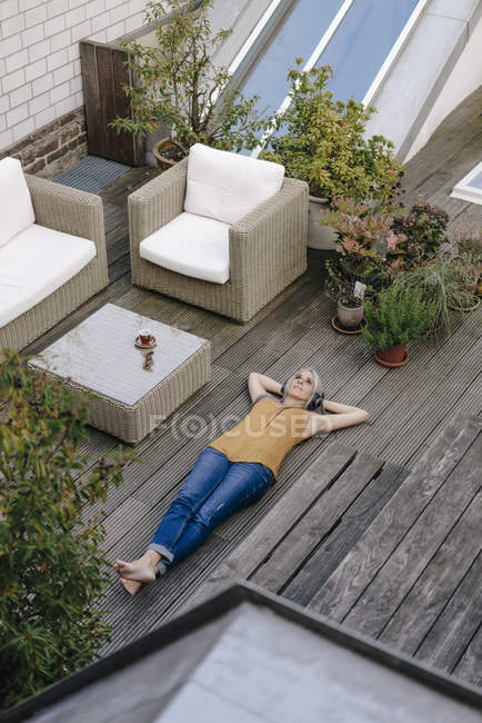 Woman relaxing on terrace and listening music with headphones — Stock Photo