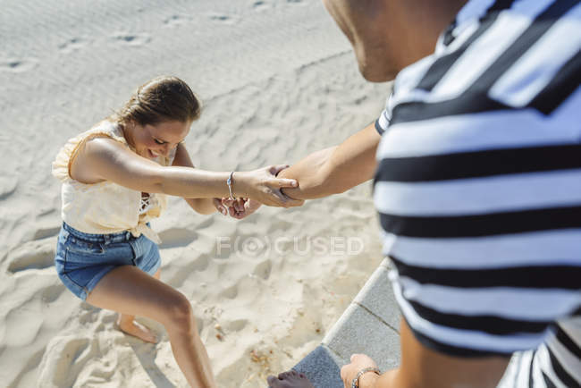 Man helping woman to climb up from the beach — Stock Photo