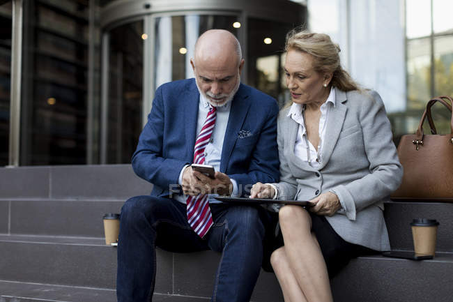 Senior businessman and businesswoman sitting on stairs using cell phone and tablet — Stock Photo