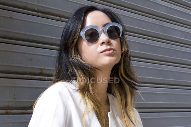 Retrato de la joven que usa gafas de sol de moda - foto de stock