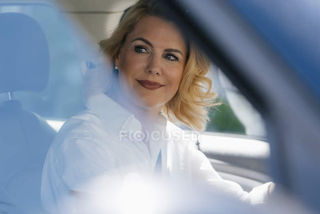 Smiling businesswoman in car looking sideways — Stock Photo
