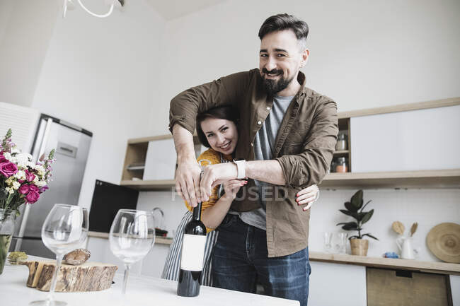 Retrato de pareja feliz con botella de vino tinto en la cocina. - foto de stock