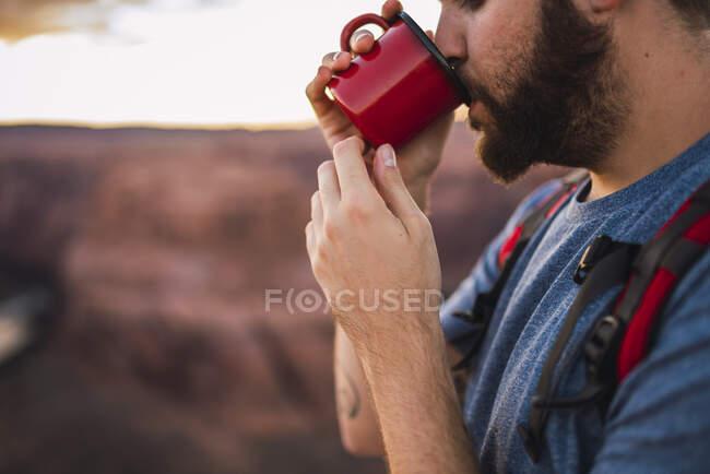 Jóvenes que beben, taza roja - foto de stock