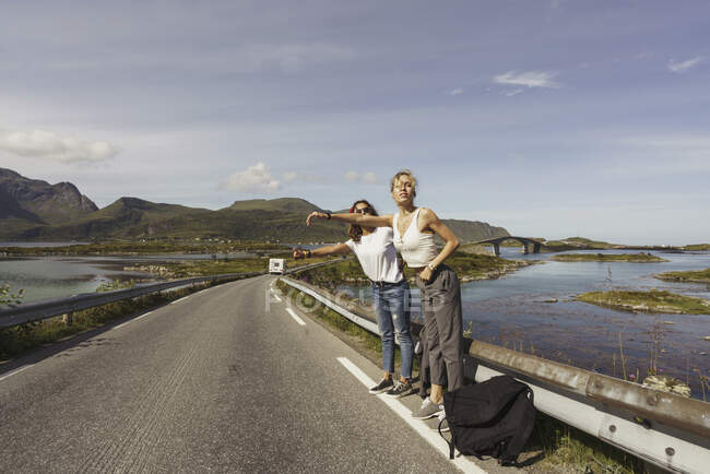 Young women hitchhiking on an empty road, Lapland, Norway — Stock Photo