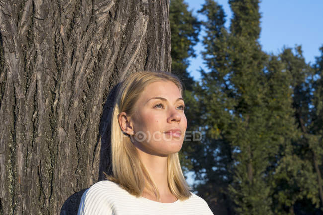 Portrait of daydreaming blond woman leaning at tree trunk and looking at distance — Stock Photo