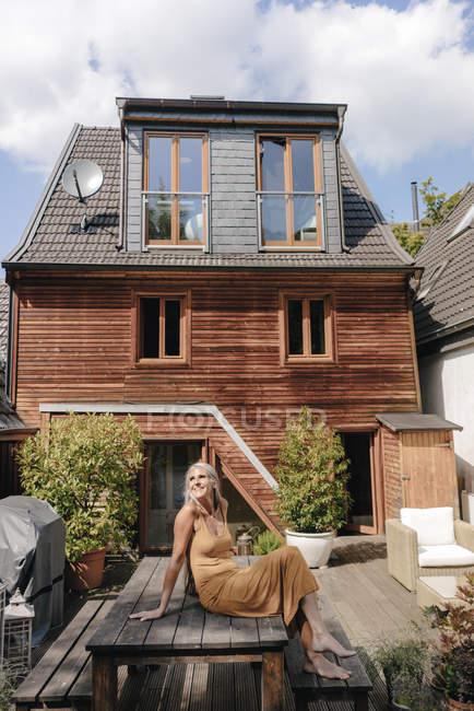 Donna felice seduta sulla terrazza di casa sua — Foto stock