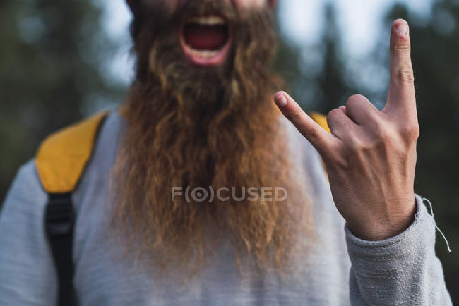 Крупный план кричащего человека с бородой, делающего знак рога — стоковое фото
