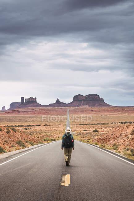 США, Юта, людина з рюкзаком, що йде по дорозі в долину пам