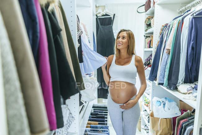 Donna incinta che guarda i vestiti in uno spogliatoio — Foto stock
