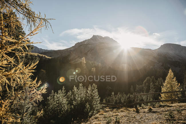 Switzerland, Sun behind the mountains - foto de stock