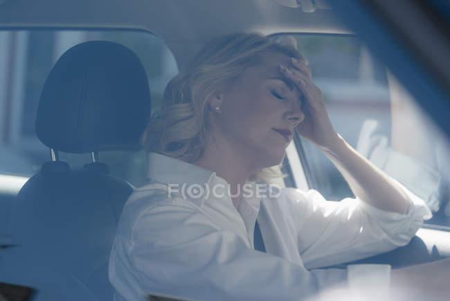 Mujer rubia seria en coche - foto de stock
