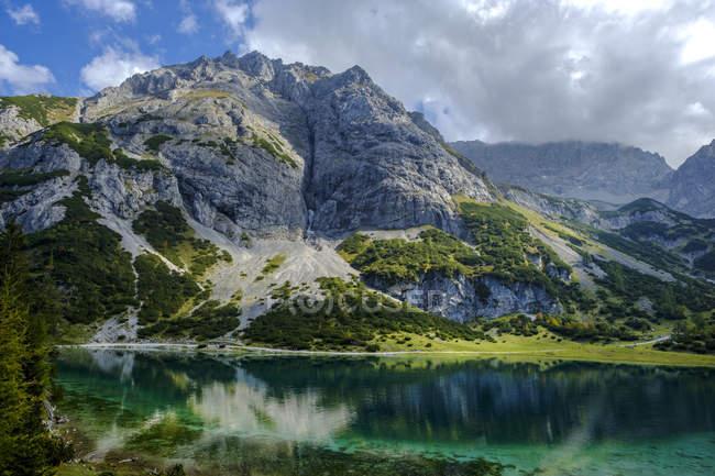 Austria, Tirol, Montes Wetterstein, Mieminger Kette, Ehrwald, Lago Seebensee y Vorderer Tajakopf - foto de stock