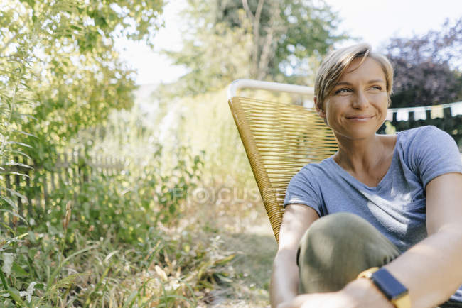 Женщина сидит в саду на стуле — стоковое фото