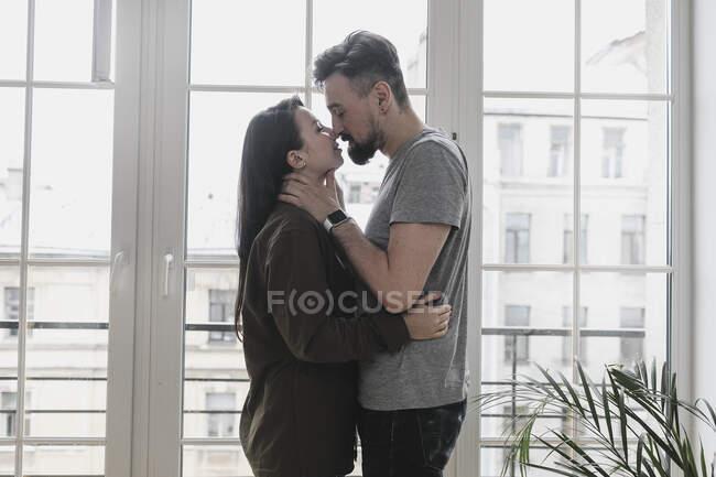 Couple heureux embrassant à la maison — Photo de stock