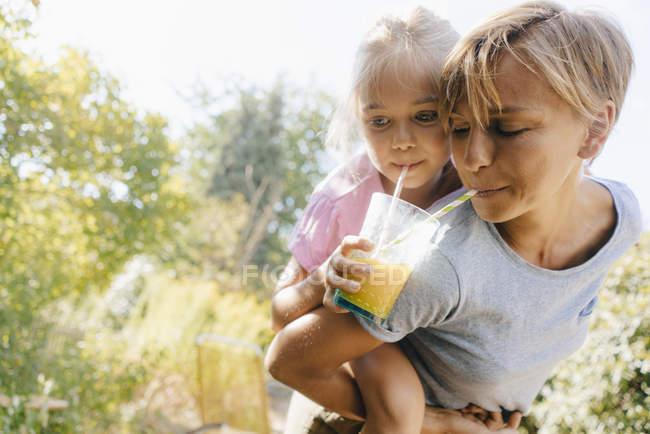 Mère portant fille piggyback dans le jardin et boire un smoothie — Photo de stock