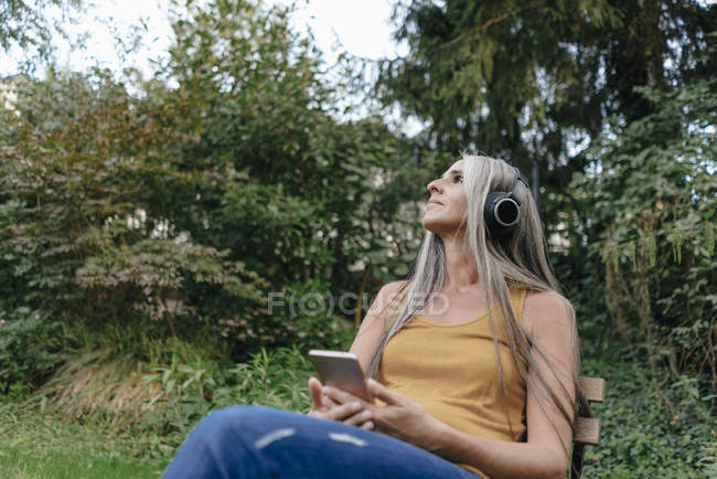 Woman with cell phone sitting in the garden and listening music with headphones — Stock Photo